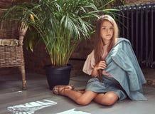 Niña linda con el pelo marrón largo que lleva un vestido elegante, sentándose en un piso de madera en un cuarto con un interior d Fotografía de archivo libre de regalías