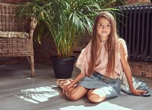 Niña linda con el pelo marrón largo que lleva un vestido elegante, sentándose en un piso de madera en un cuarto con un interior d Imagen de archivo libre de regalías