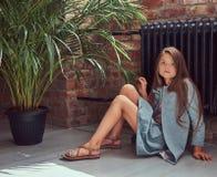 Niña linda con el pelo marrón largo que lleva un vestido elegante, sentándose en un piso de madera en un cuarto con un interior d Fotos de archivo