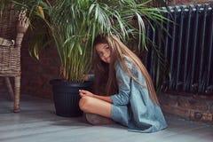 Niña linda con el pelo marrón largo que lleva un vestido elegante, sentándose en un piso de madera en un cuarto con un interior d Imagenes de archivo