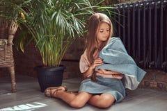 Niña linda con el pelo marrón largo que lleva un vestido elegante, sentándose en un piso de madera en un cuarto con un interior d Fotografía de archivo