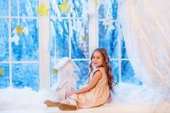Niña linda con el pelo rizado en la ventana antes de magia de la Navidad y del Año Nuevo foto de archivo libre de regalías