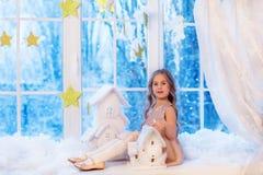 Niña linda con el pelo rizado en la ventana antes de magia de la Navidad y del Año Nuevo fotos de archivo