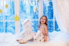 Niña linda con el pelo rizado en la ventana antes de magia de la Navidad y del Año Nuevo imagenes de archivo