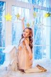 Niña linda con el pelo rizado en la ventana antes de magia de la Navidad y del Año Nuevo fotografía de archivo libre de regalías