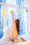 Niña linda con el pelo rizado en la ventana antes de magia de la Navidad y del Año Nuevo foto de archivo
