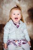 Niña linda con el pelo rubio que se sienta en silla y la risa Fotos de archivo