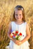 Niña linda con el ramo rojo de la amapola de las flores salvajes Imagen de archivo libre de regalías