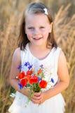 Niña linda con el ramo rojo de la amapola de las flores salvajes en el summ Imagenes de archivo