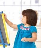 Niña linda con el tablero de dibujo imágenes de archivo libres de regalías