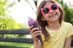 Niña linda con helado delicioso en banco en parque fotos de archivo libres de regalías