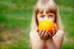 Niña linda con la fruta anaranjada en manos, concepto sano de la comida imagen de archivo libre de regalías