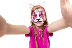 Niña linda con la máscara pintada en la cara que hace el selfie Fotos de archivo libres de regalías