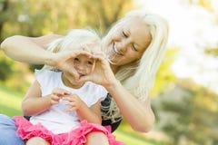 Niña linda con la madre que hace forma del corazón con las manos Foto de archivo