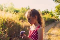 Niña linda con las flores en el prado en día de verano Imagenes de archivo
