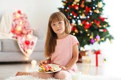 Niña linda con las galletas en el sitio adornado para la Navidad Т Imagenes de archivo
