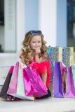 Niña linda con los bolsos coloridos para hacer compras en supermercado Fotografía de archivo