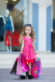 Niña linda con los bolsos coloridos para hacer compras en supermercado Imágenes de archivo libres de regalías