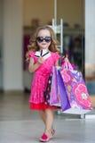 Niña linda con los bolsos coloridos para hacer compras en supermercado Imagenes de archivo