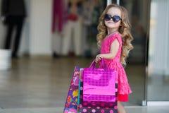 Niña linda con los bolsos coloridos para hacer compras en supermercado Imagen de archivo libre de regalías
