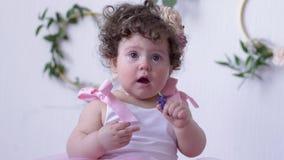 Niña linda con los ojos grandes y el pelo rizado en el primer rosado del vestido que presenta en el estudio blanco almacen de video