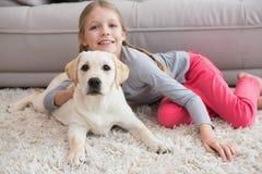 Niña linda con su perrito en el sofá imagenes de archivo