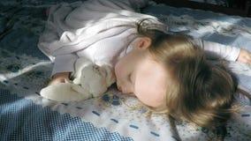 Niña linda con sueños del pelo rubio dulce en la cama en su panza encendida por la sol con un abrazo del conejito del peluche almacen de metraje de vídeo