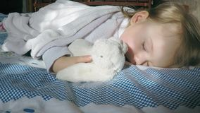 Niña linda con sueños del pelo rubio en la cama en su panza encendida por el sol con un abrazo del conejito del peluche almacen de metraje de vídeo