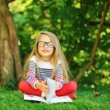 Niña linda con un libro en un parque verde del verano Imagen de archivo