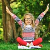 Niña linda con un libro en un parque verde del verano con las manos r Foto de archivo libre de regalías