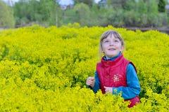 Niña linda de la sonrisa en el prado en día de primavera Foto de archivo libre de regalías