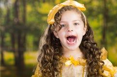 Niña linda del Headshot que lleva el vestido amarillo hermoso con la banda principal a juego, presentando para la cámara, bosque  Imagen de archivo libre de regalías