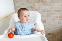 Niña linda del niño que come la comida sana en guardería Bebé en silla foto de archivo