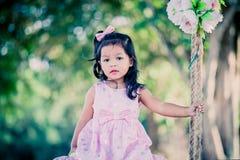 Niña linda del niño que se sienta en el oscilación en el parque Imágenes de archivo libres de regalías