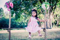 Niña linda del niño que se sienta en el oscilación en el parque Fotografía de archivo