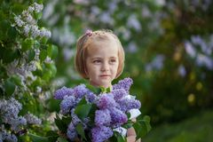 Niña linda del retrato de Clooseup con un ramo de lilas en primavera imagen de archivo