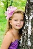 Niña linda del retrato que se coloca cerca del árbol Foto de archivo