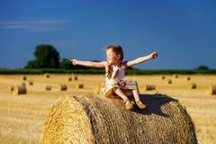 Niña linda divertida que presenta en el pajar en campo del verano Imágenes de archivo libres de regalías