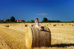 Niña linda divertida que presenta en el pajar en campo del verano Fotografía de archivo