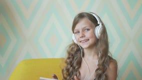 Niña linda en auriculares que escucha la música usando una tableta, mirando la cámara y sonriendo en casa metrajes