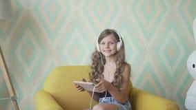Niña linda en auriculares que escucha la música usando una tableta, mirando la cámara y la sonrisa almacen de video
