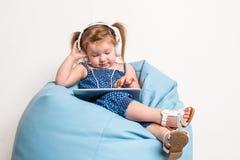 Niña linda en auriculares que escucha la música usando una tableta y que sonríe mientras que se sienta en bolso grande azul Foto de archivo