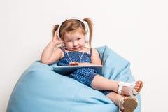 Niña linda en auriculares que escucha la música usando una tableta y que sonríe mientras que se sienta en bolso grande azul Imagenes de archivo