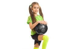 Niña linda en camisa verde con el balón de fútbol en manos Imagenes de archivo