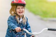 Niña linda en chaqueta del casco y del dril de algodón en una bici Foto de archivo libre de regalías