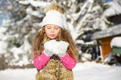 Niña linda en copos de nieve que soplan del sombrero caliente de las manos Imagenes de archivo