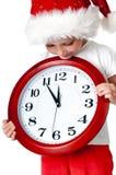 Niña linda en el casquillo de santa con un reloj Imagen de archivo libre de regalías