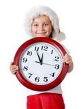 Niña linda en el casquillo de santa con un reloj Fotos de archivo libres de regalías