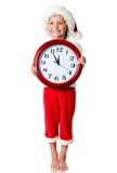 Niña linda en el casquillo de santa con un reloj Foto de archivo libre de regalías