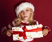 Niña linda en el sombrero de santa que lleva a cabo el regalo de Navidad Fotografía de archivo libre de regalías